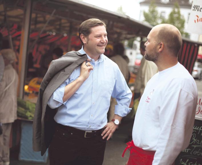 Schnell mit der Zunge: Tim Kurzbach (SPD,  l.) ist jemand,  der den Kontakt zu den Menschen sucht und braucht– so wie gestern Morgen auf dem Ohligser Wochenmarkt im Gespräch mit Rudolf Jacobs Foto: Christian Beier
