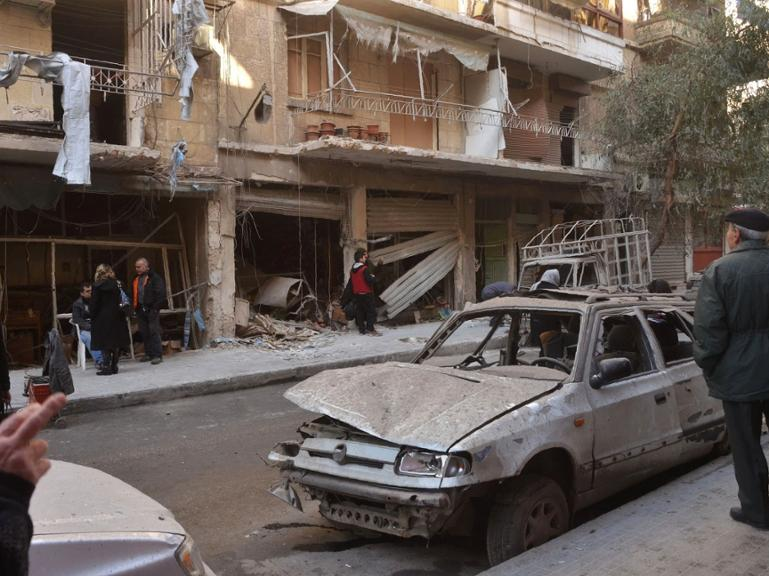 Syrian residents look at the damage following reported rebel shelling in Aleppo&#39s government-controlled neighbourhood of Suleimaniyeh, on February 14, 2016. / AFP / GEORGE OURFALIAN